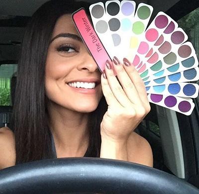 Mulher de cabelos escuros sorri e segura cartela de cores de Coloração Pessoal, cobrindo metade do rosto. Foto: Instagram @julianapaes.