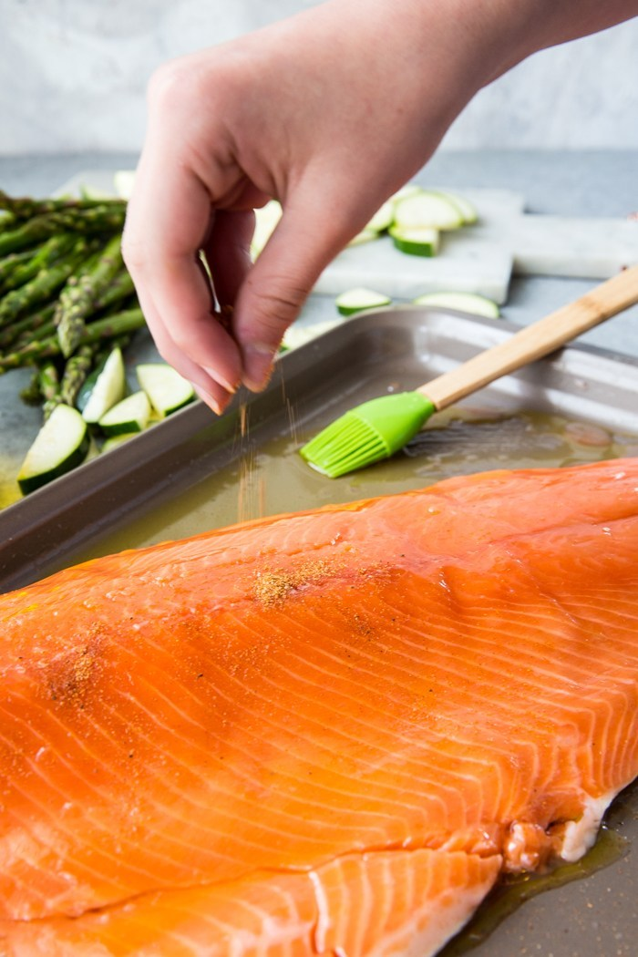 A hand seasoning a fillet of coho salmon with cajun spices