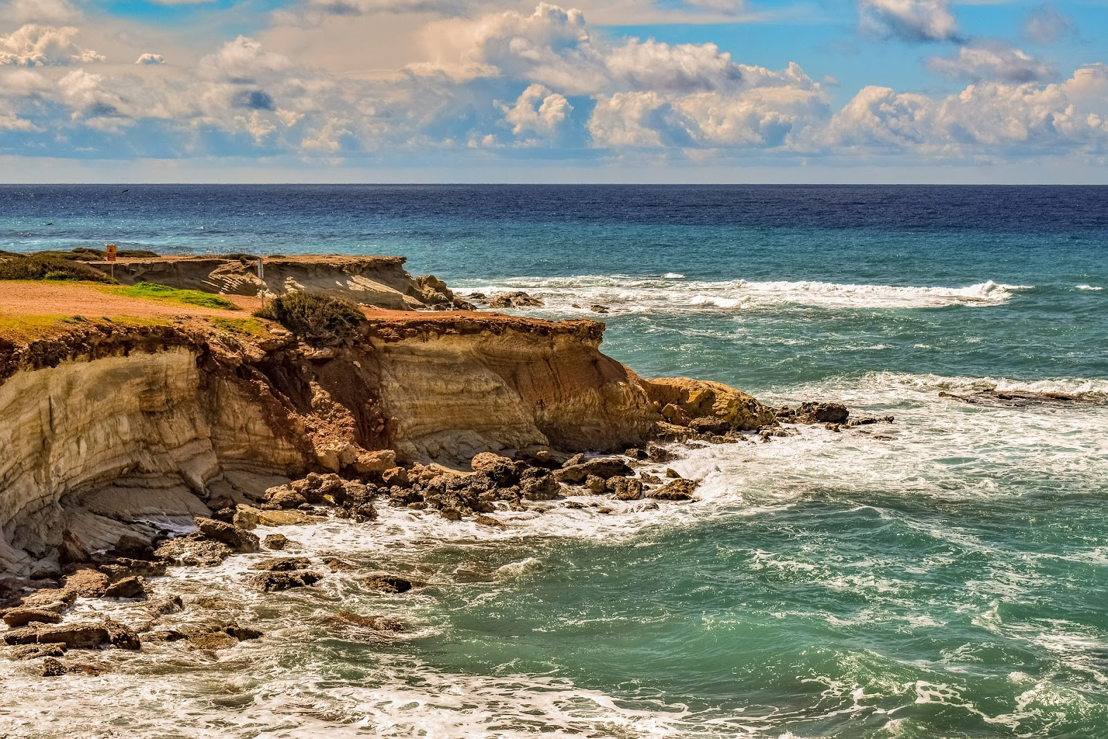 paphos shore, dramatic coastline with cliffs and blue water hitting the coast. cloudy yet sunny day in cyprus