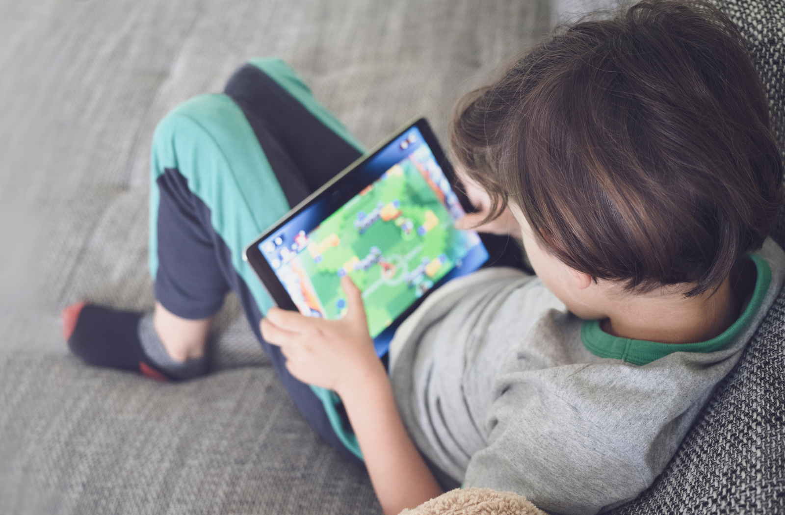 Child playing a game on a tablet potentially at risk of digital eye strain.