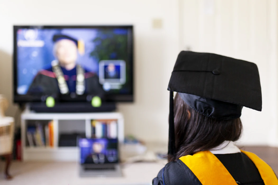 A student in cap and gown sits in front of a screen streaming a live graduation ceremony