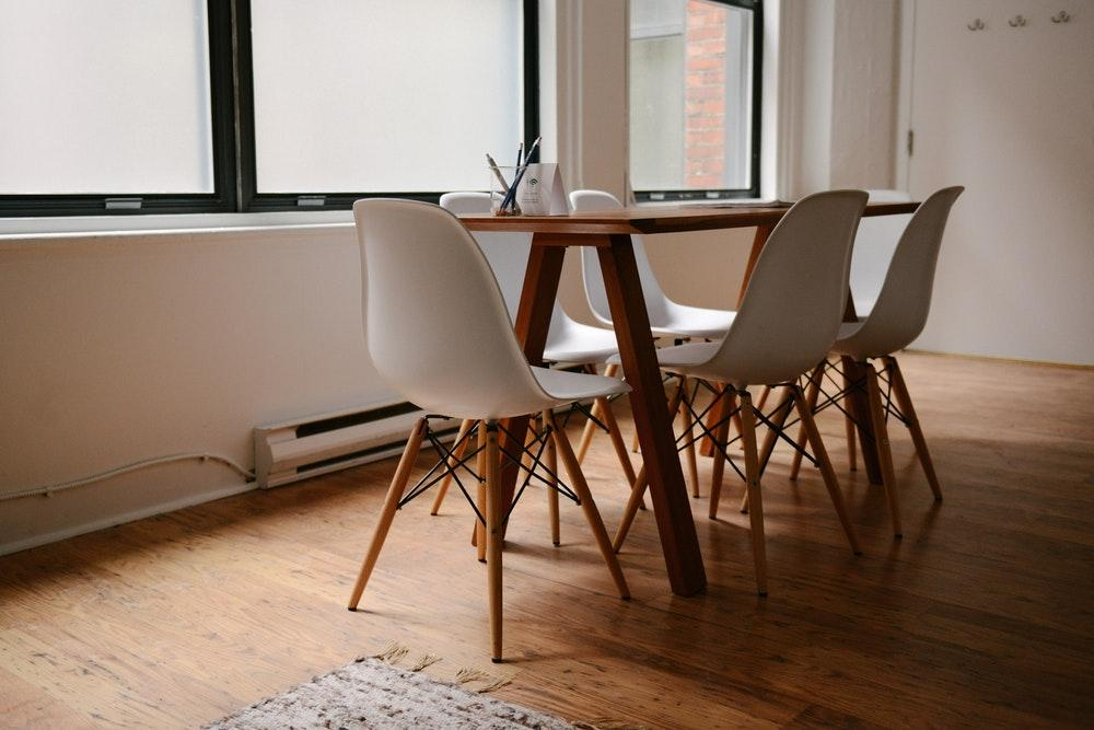 An interior of a meeting room stocked with modern wooden chairs and table in an office space