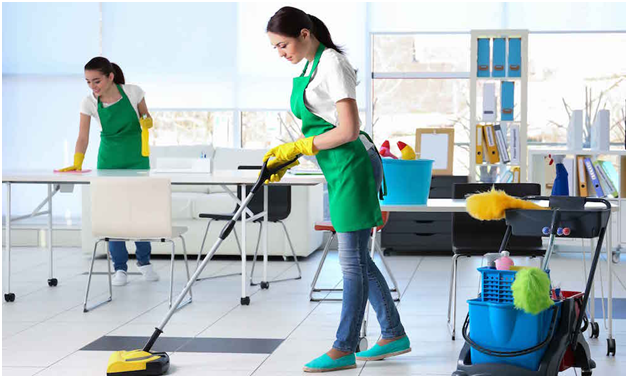 women with green uniform apron and yellow gloves cleaning floor and table of an office