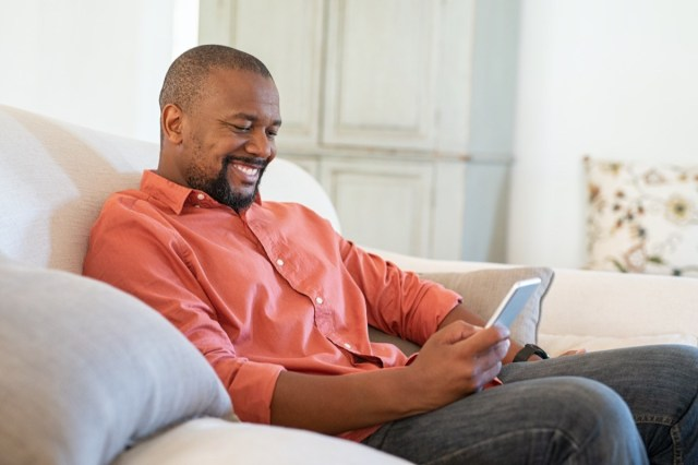 man using smart phone while relaxing at home. Smiling mature man at home sitting on couch reading phone message.