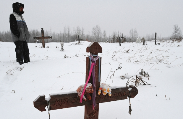 A father, who can only be identified as Merle, visits the grave site of his infant daughter at the Paul First Nation. She died while in foster care and the parents are suing the government for $1 million.