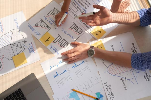 Top view of creative team discussing business graphs drawn in marker pens Free Photo