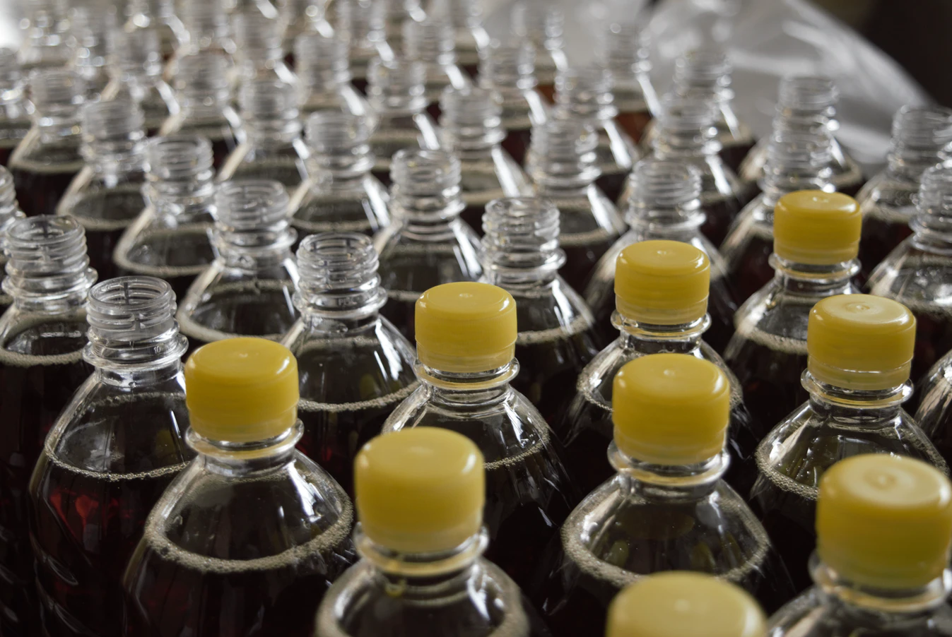 assembly line of soda bottles and caps