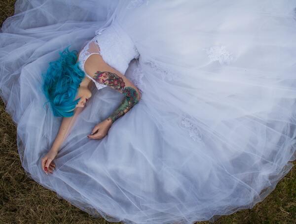 Foto de uma mulher de cabelo azul deitada na grama com a barra do vestido em volta dela