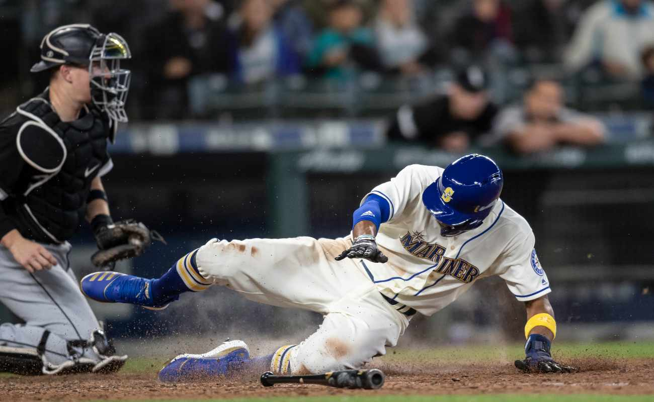 Seattle Mariners' player Keon Broxton slides into home plate safely in front of the catcher
