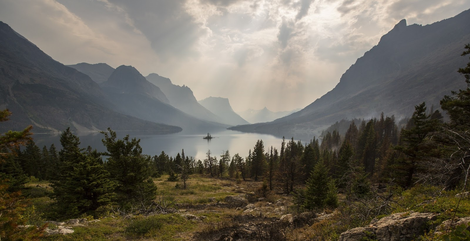 Photo of a mountain lake, with sunshine streaming through the clouds.