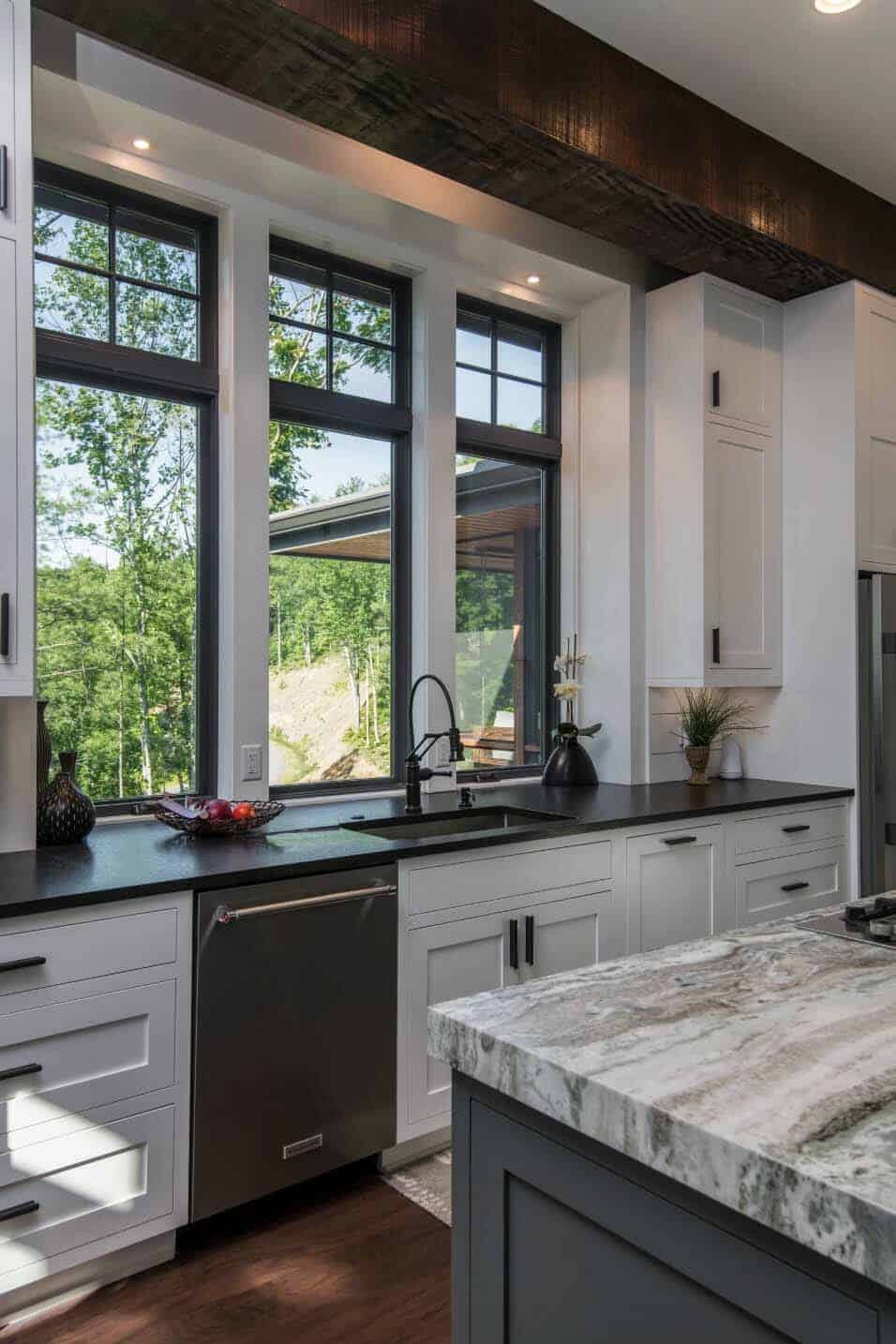 this kitchen features white cabinets and black countertops with a grey center island. inset white shaker cabinets are adorned with matte black hardware. the room is flooded with natural light by three large windows