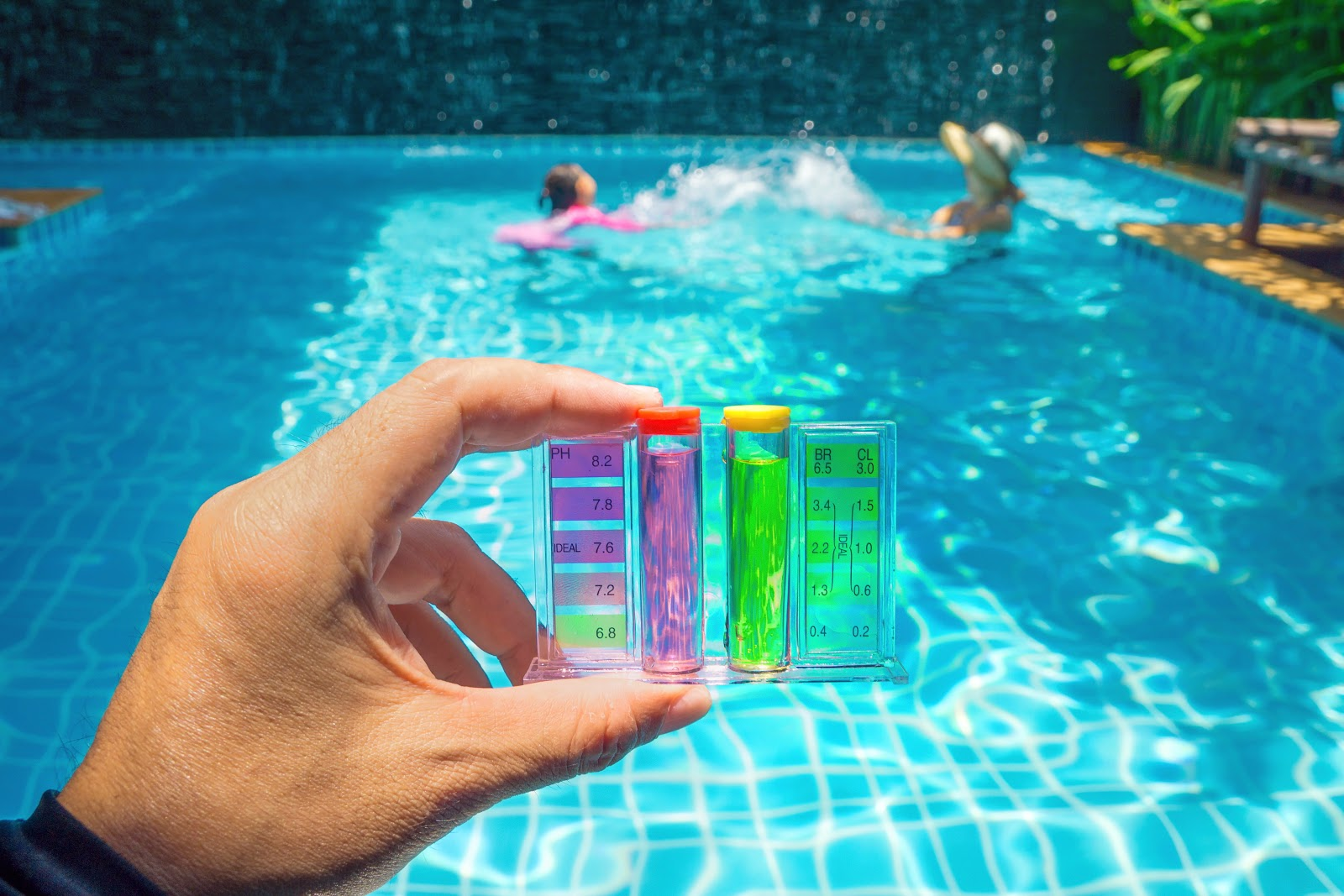 holding a pink and green test kit next to an inground pool where a woman and young girl are swimming
