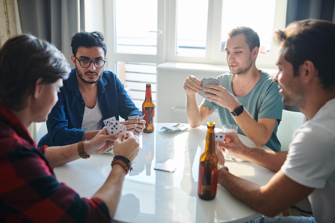 A group of people sitting around a table playing cards  Description automatically generated with medium confidence