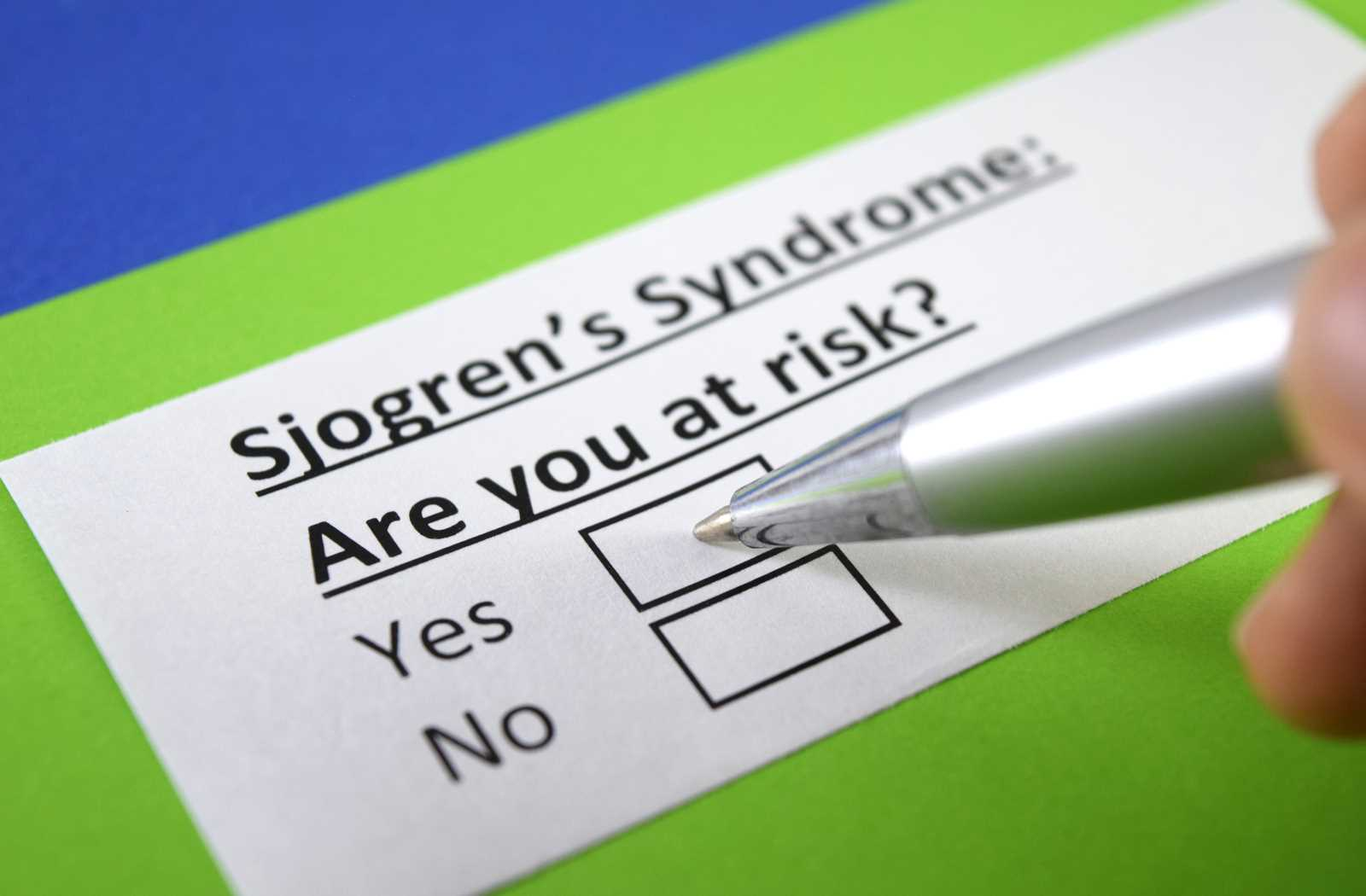 Silver pen and green and blue paper questionnaire for sjogren's syndrome asking if you're at risk