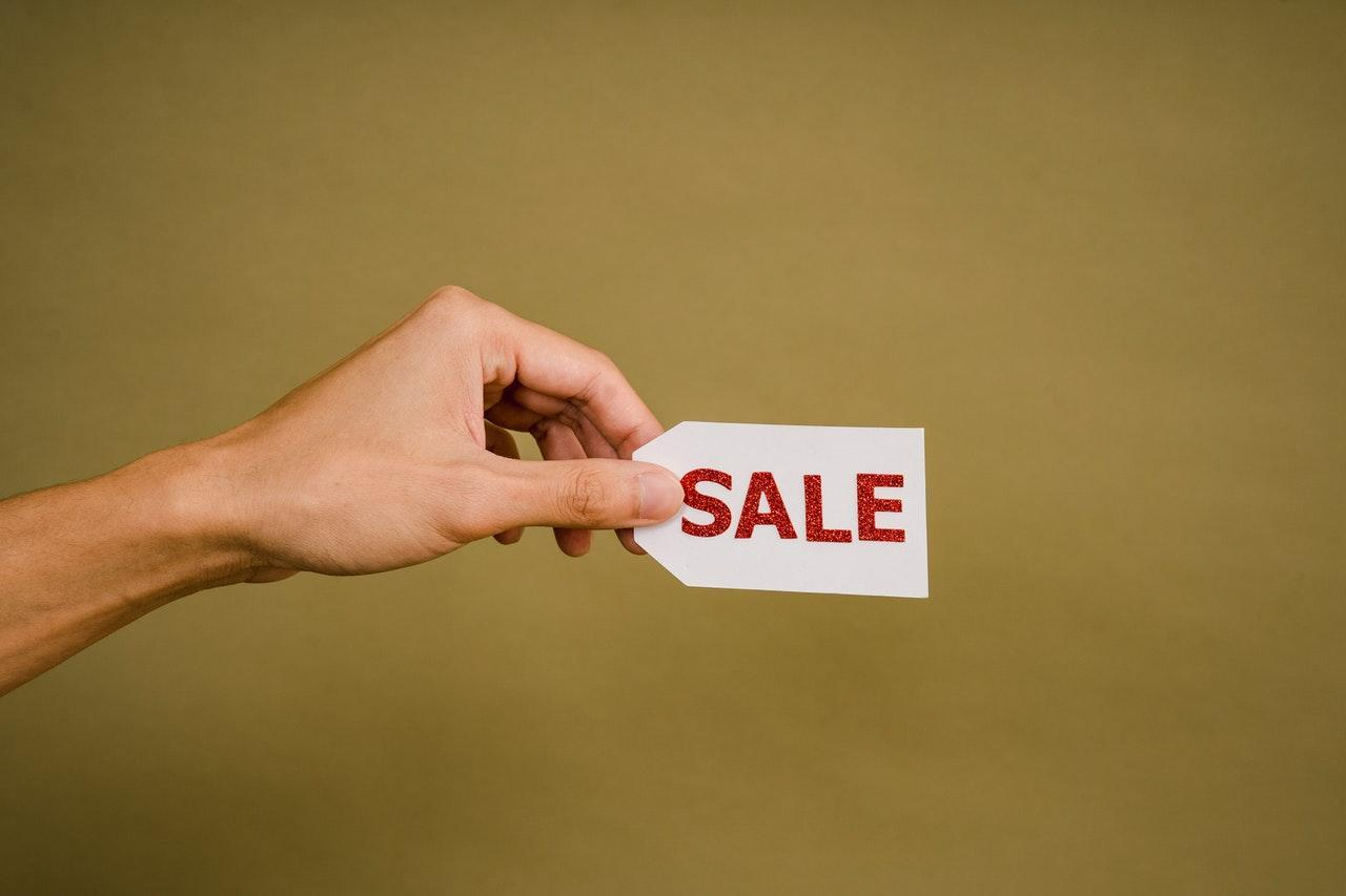 Person holding a sale tag against a mustard background