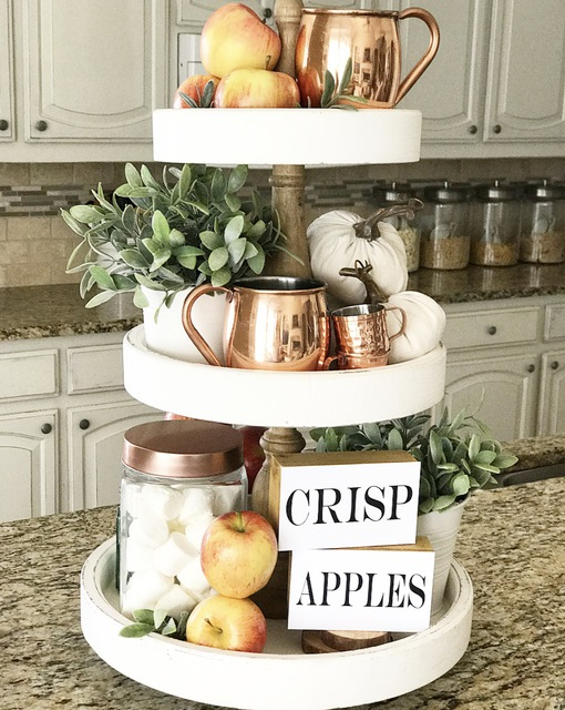 white 3 tiered tray on kitchen countertop with pumpkins, copper mugs, mini signs, fresh apples and fake plants