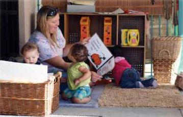 A caregiver reading a book to two toddlers