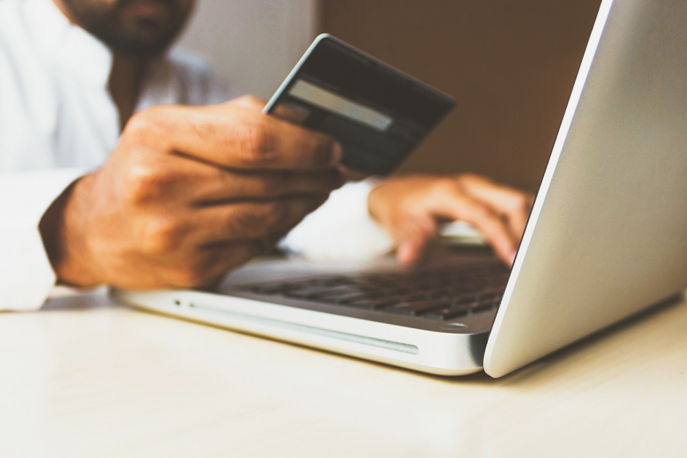 person typing credit card details into laptop