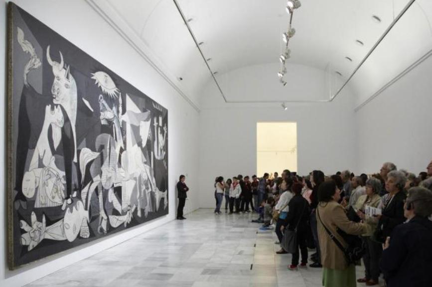 Pessoas observam a obra de Picasso (Guernica).