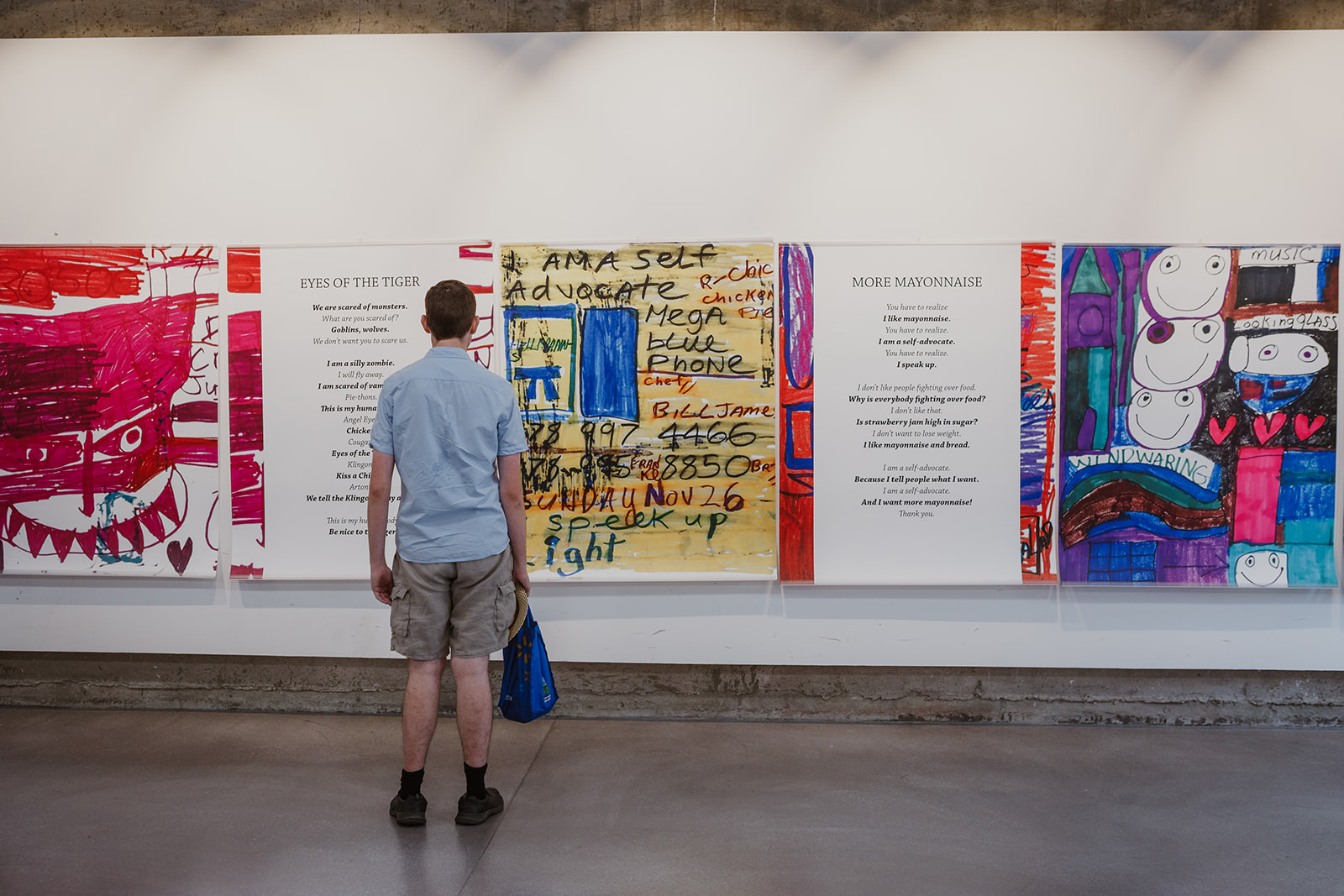 A visitor stands in front of Teresa's colourful artwork and self-talk poetry at the opening of Born To Represent on July 22, 2019. Photo: This Is It Studios.