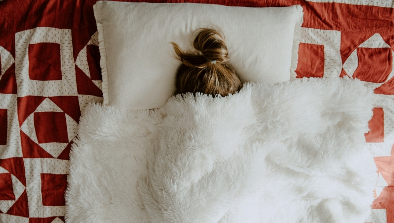 woman sleeping under soft throw blanket