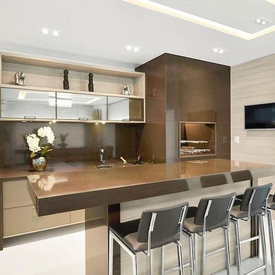 Área gourmet com churrasqueira e bancada revestidas de porcelanato marmorizado, armários de madeira e bancos pretos.