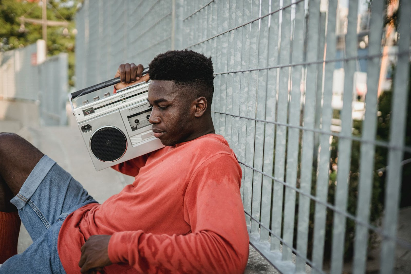 A man wearing a read t-shirt and blue jeans listening something on a vintage radio -How to Get Your Music on Radio