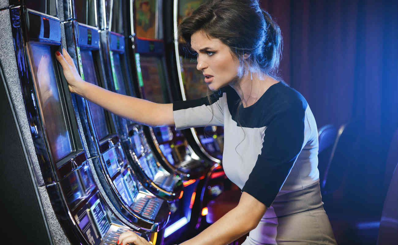 woman is losing during slot machines game in a casino