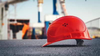 red hard hat on pavement\