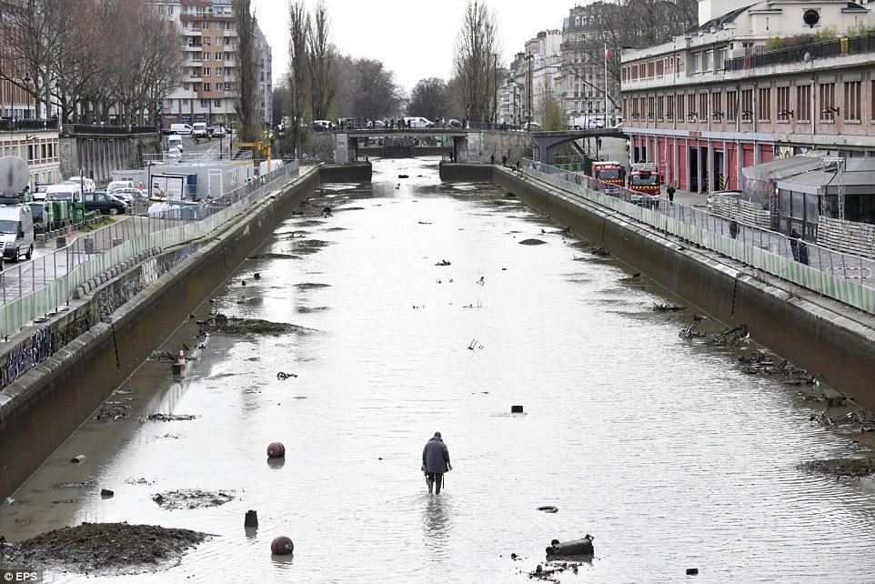 清理行動:一名男子在巴黎最時尚的地區之一的中心穿過聖馬丁運河的最後一趟