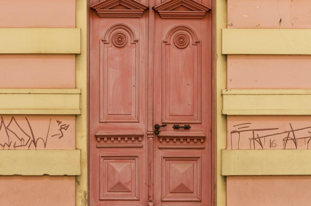 photo of pink wooden door on pink wall