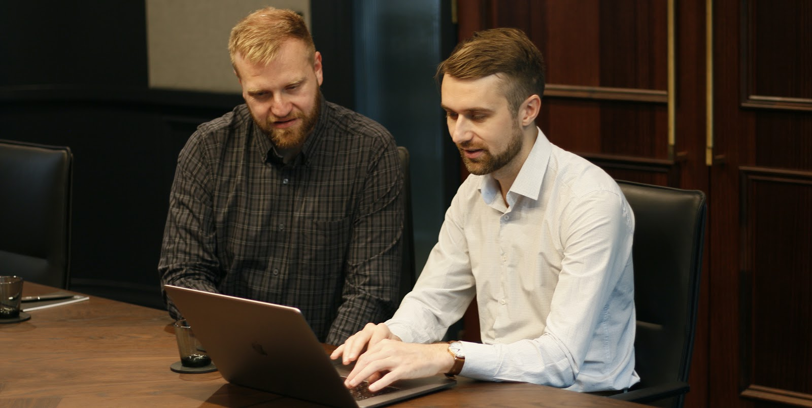 Two people investigating FTP clients on laptop.