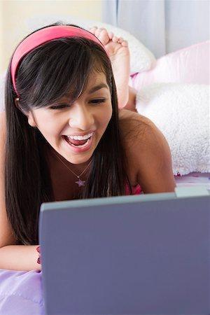 young girl enjoying orkutchat radio while chatting on laptop