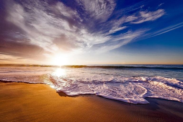 Praia com nuvens ao entardecer ensolarado