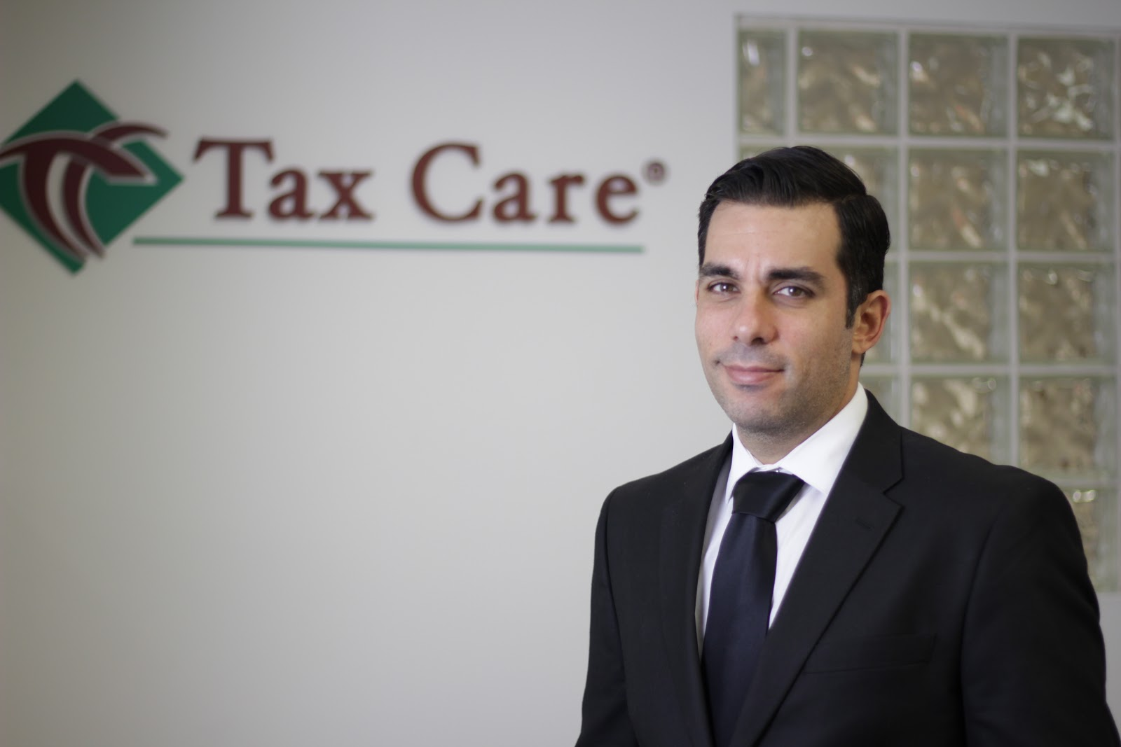Tax Care's employee posing in front of signage