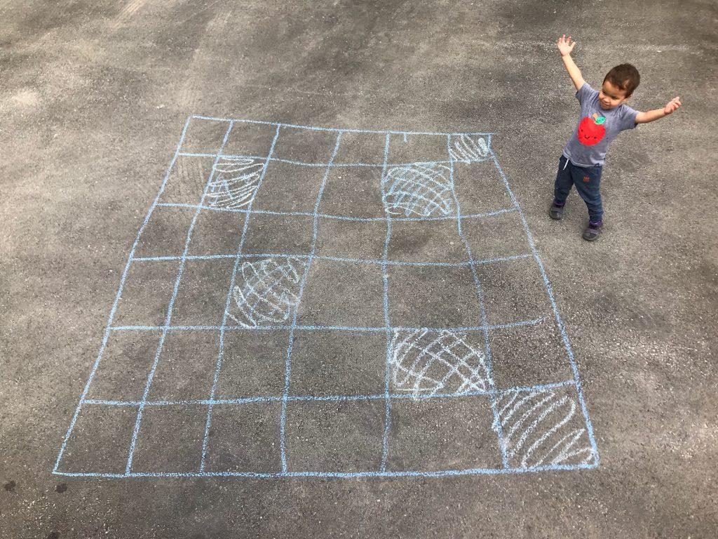 This shows a little boy beside a 6x6 grid of chalk squares on asphalt. Some of the squares are colored.