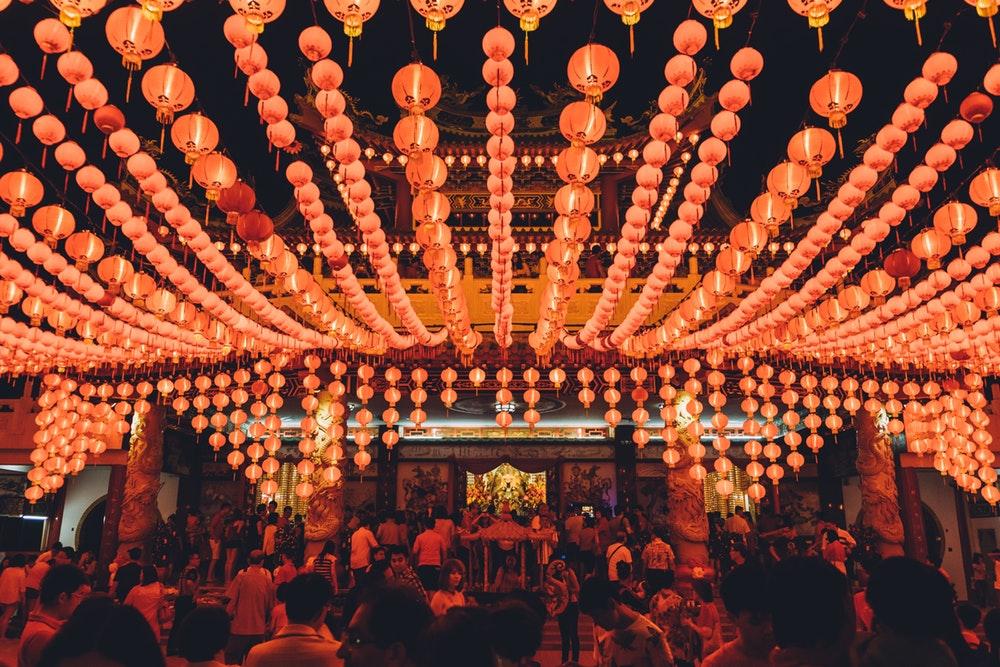 people gathering under orange paper lanterns