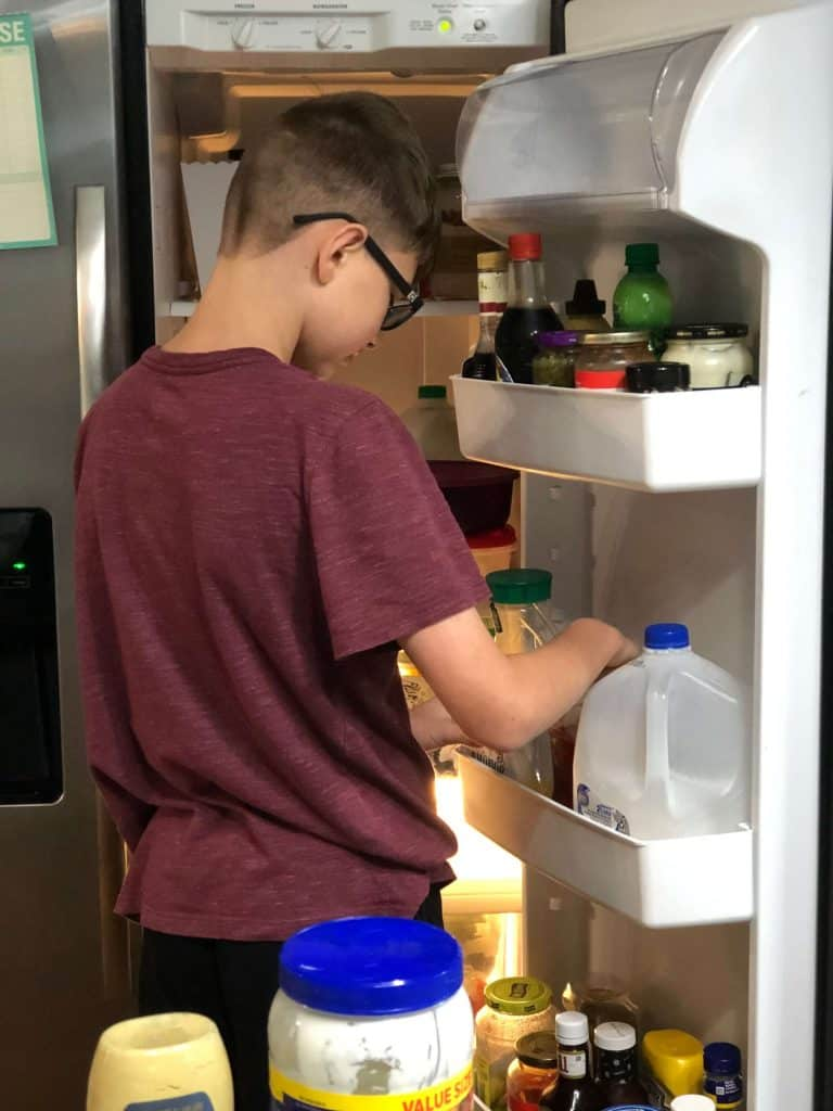 Age appropriate chores for 13-15 year olds: Photo of young teen boy cleaning out the refrigerator
