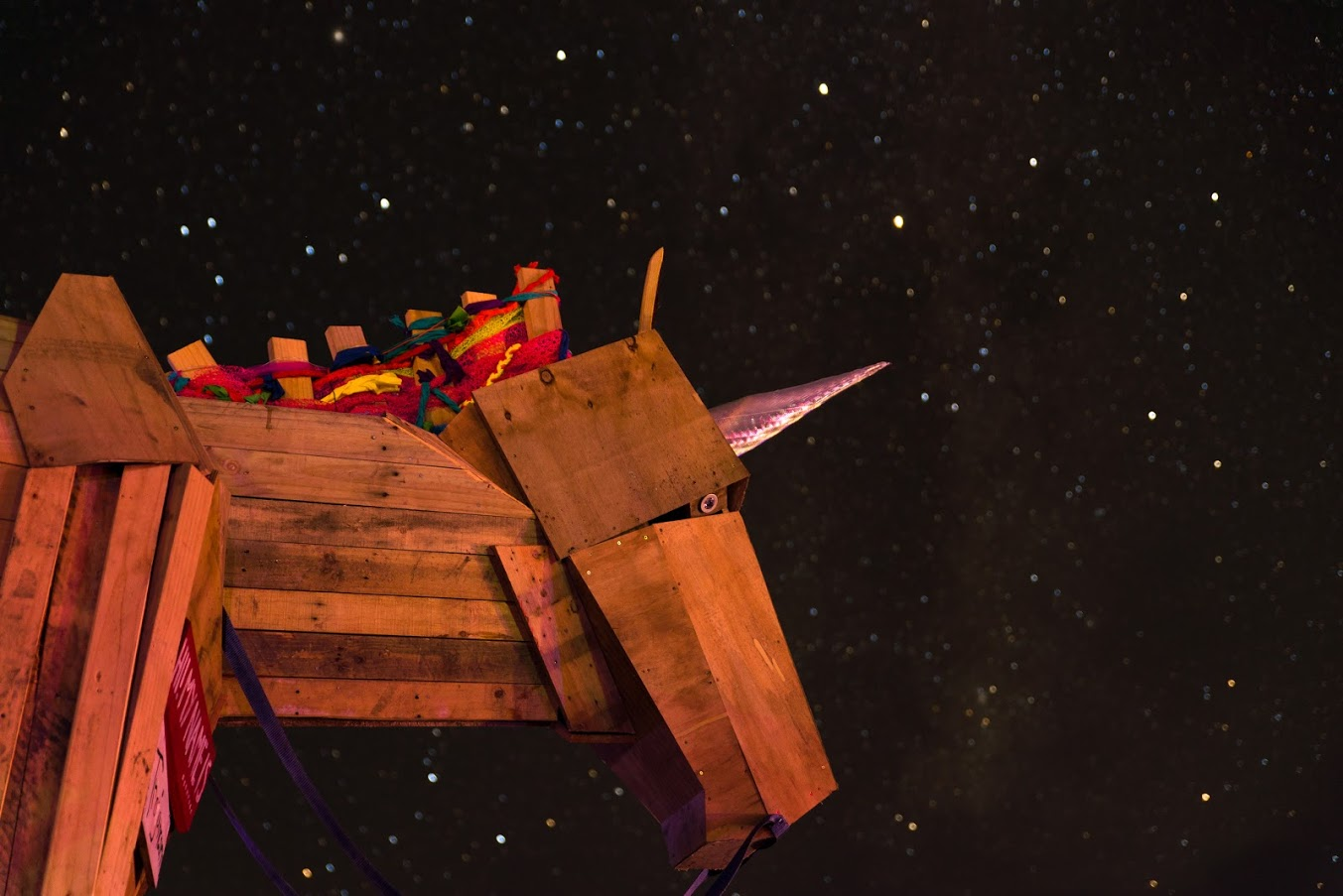 A unicorn sculpture made of wood with the starry night sky in the background.