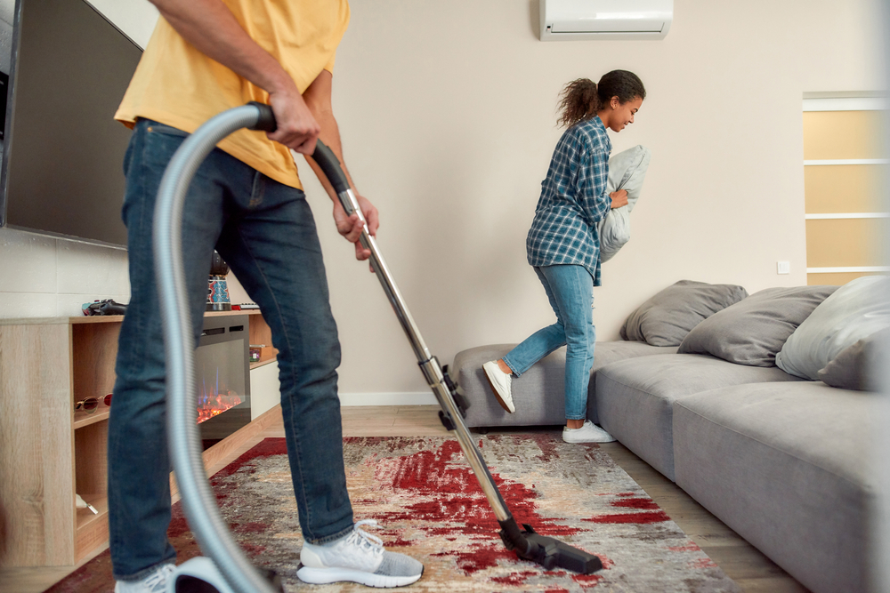 man vacuuming while woman fluffs pillow behind him