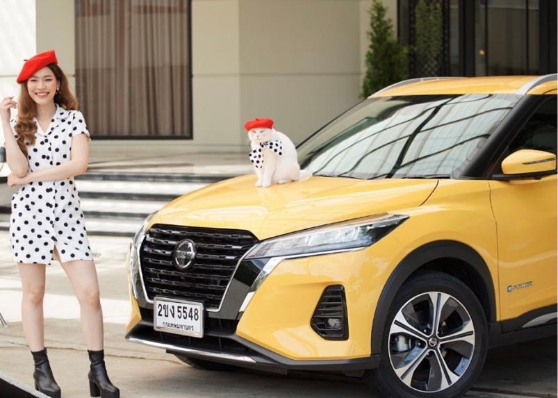 A person standing next to a yellow car with a stuffed animal on the hood  Description automatically generated with medium confidence