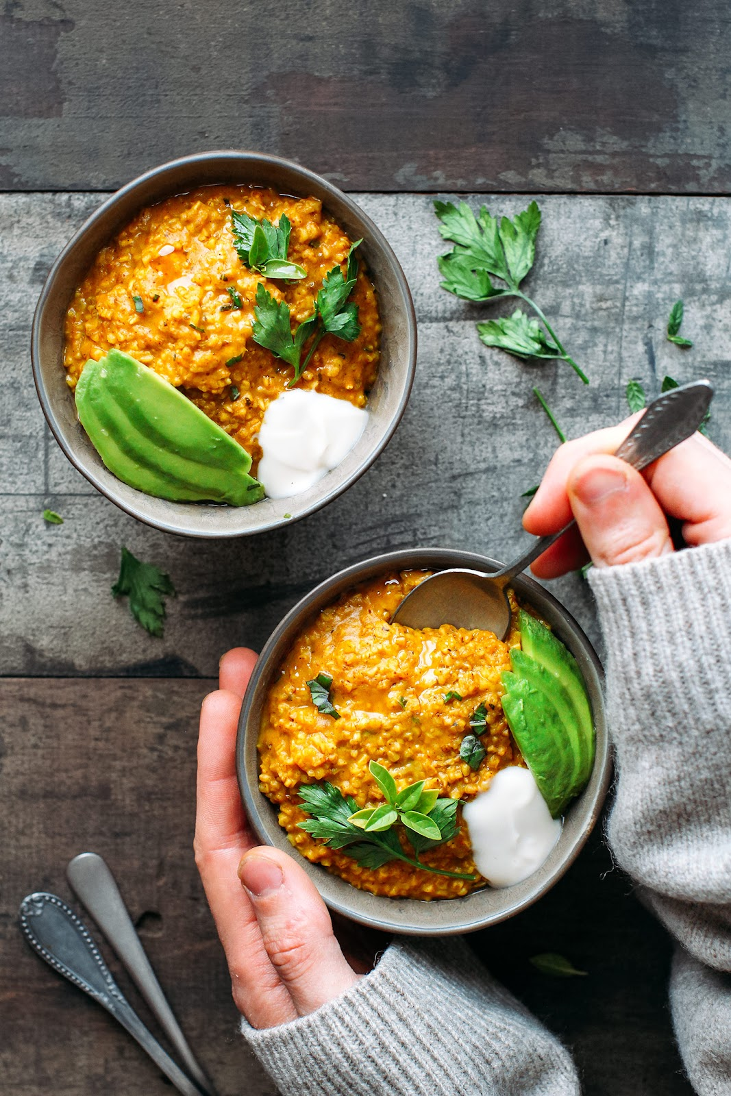 Two bowls of creamy masala steel-cut oats garnished with sliced avocado