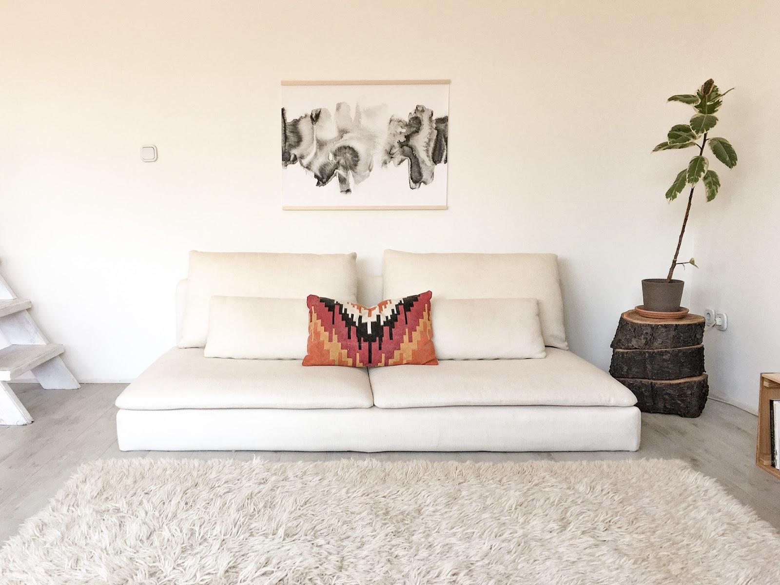 natúr kanapé és szőnyeg színes párnával