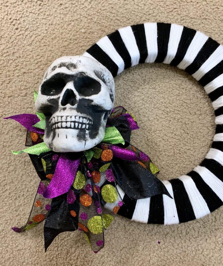 Placing the styrofoam skull head on the DIY Halloween wreath.