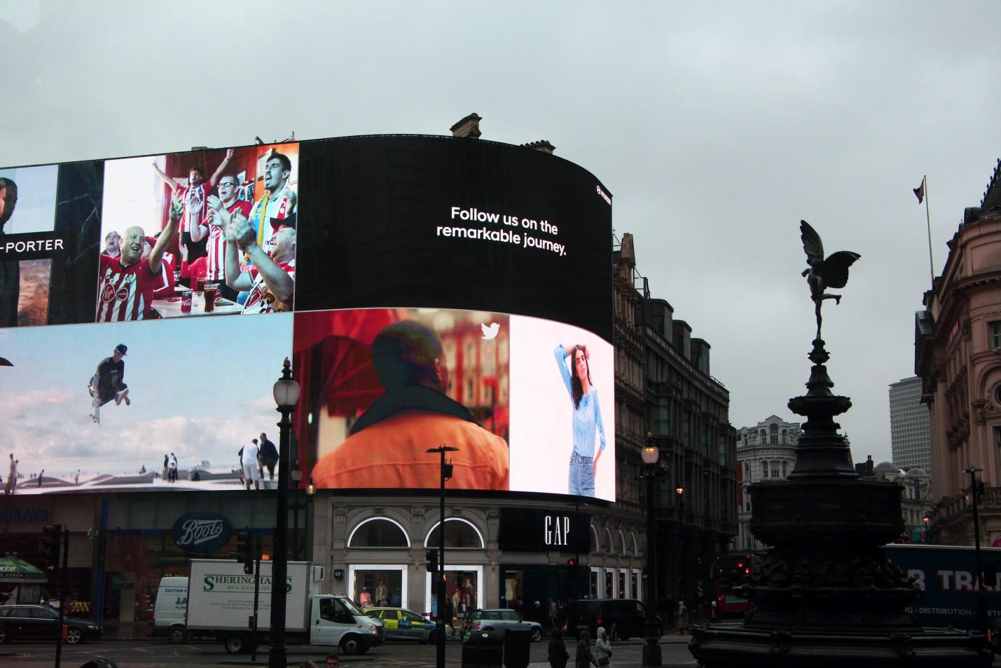 A huge digital OOH billboard with various companies promoting their products, including Net-A-Porter and Twitter.