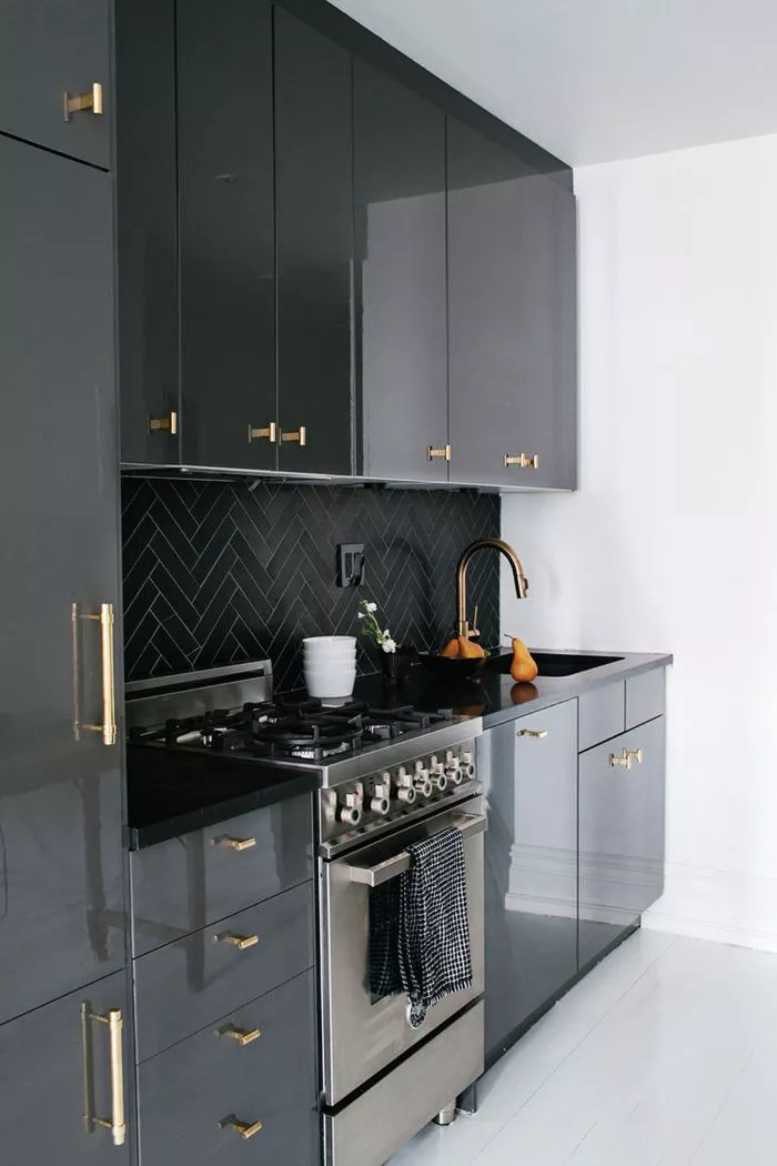 glossy grey kitchen cabinets with white walls and black herringbone backsplash gold cabinet pulls