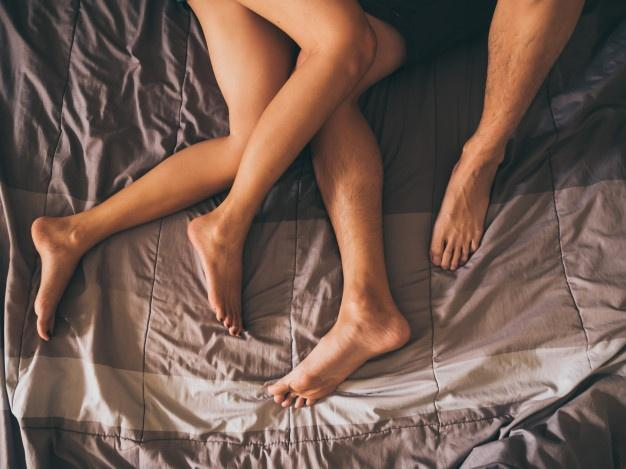 Close up of the legs of a couple on the bed.  Multiple Orgasms
