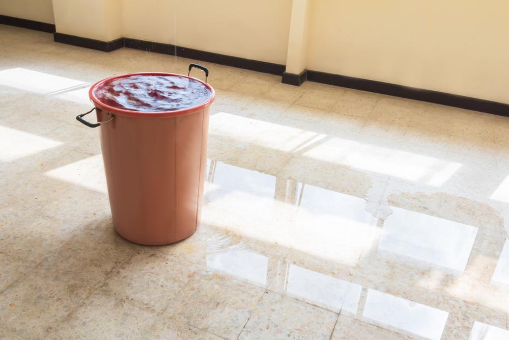 Um balde de água cheio por conta de um vazamento.