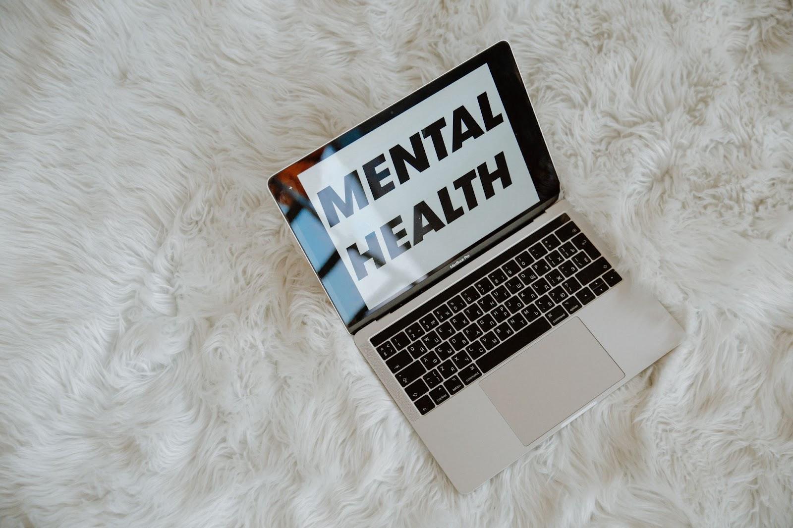 nápis mentální zdraví v notebooku položeném na koberci
