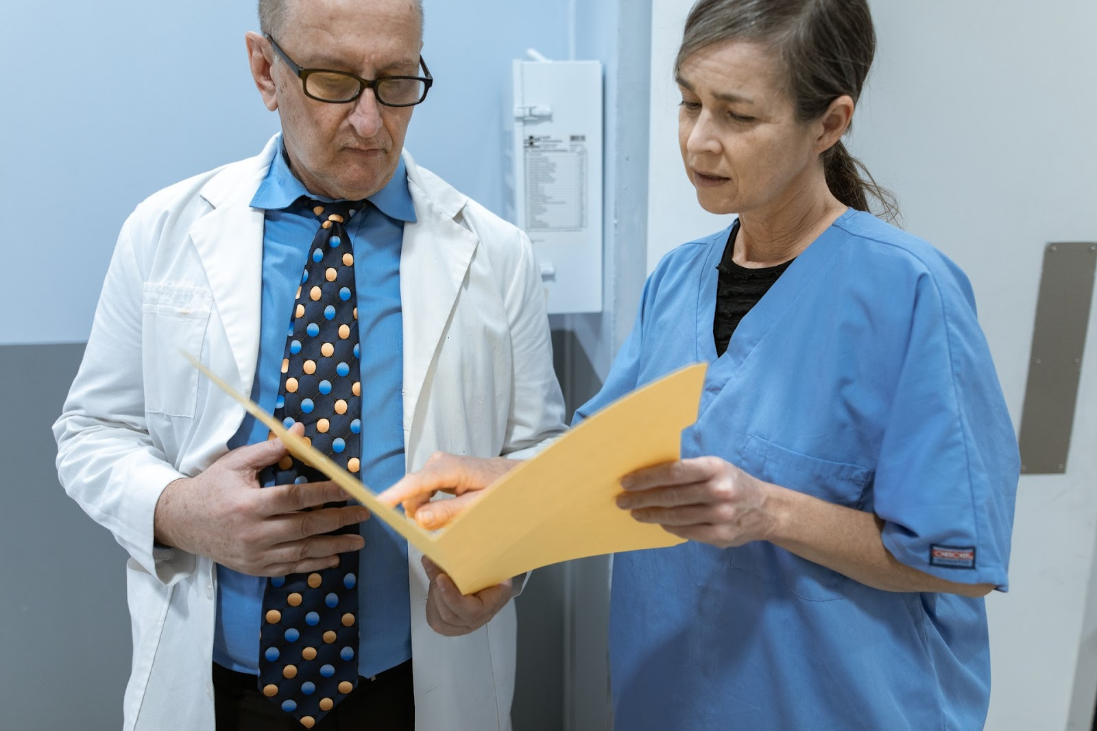 A nurse in scrubs goes over a file with a doctor in a labcoat, as they both hold the file between them in a hallway.